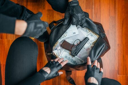 Two robbers in black uniform holds bag with money