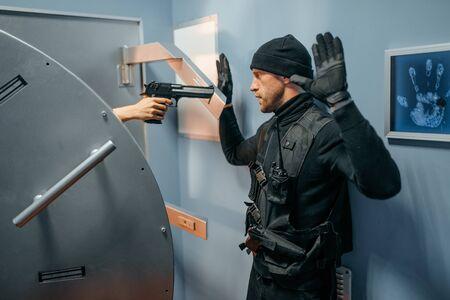 Ladrón de pie en la puerta de la bóveda con las manos en alto