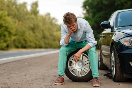 Car breakdown, tired man sitting on spare tyre Stock fotó