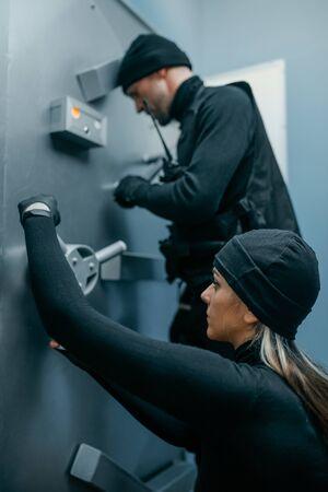 Robbers in black uniform trying to open vault lock 免版税图像