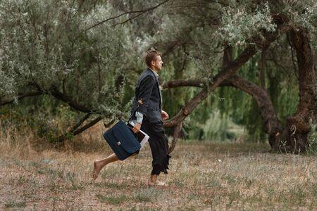 Businessman in torn suit walking on desert island Stock fotó