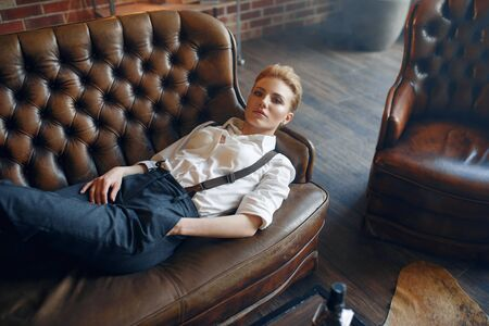 Woman with cigar lying on couch, retro fashion Reklamní fotografie