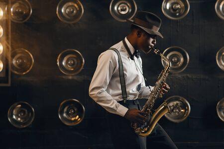 Le jazzman noir au chapeau joue du saxophone sur scène