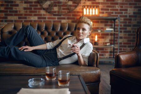 Woman lying on leather couch and smoking cigar Reklamní fotografie