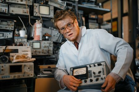 Crazy scientist holds electrical device in lab Banque d'images