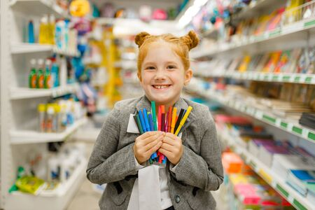 School girl holds markers, stationery store