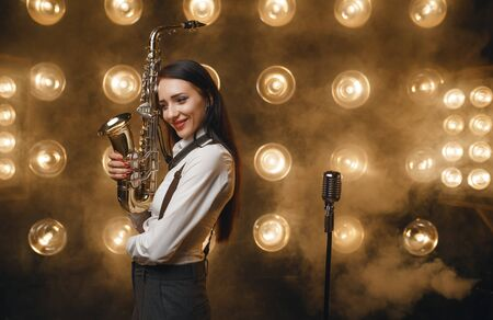 Female saxophonist poses with saxophone on stage Stock Photo