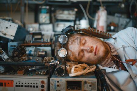 Extraño ingeniero durmiendo en dispositivos en el laboratorio