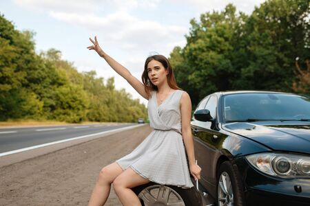 Car breakdown, young woman vote on the road