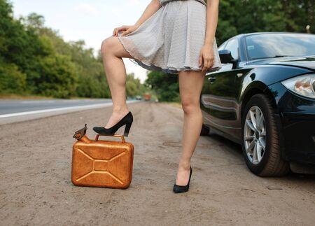 Woman with petrol canister on road, car breakdown 版權商用圖片