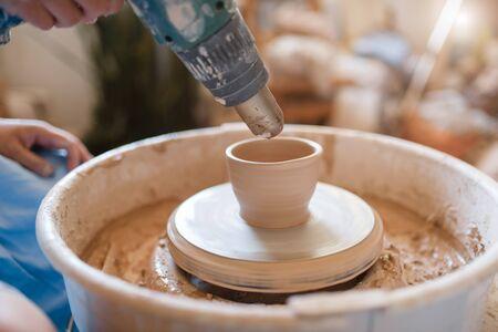 Master dries a pot on pottery wheel Stockfoto