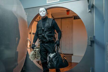 Bankoverval, overvaller in zwart uniform en masker Stockfoto