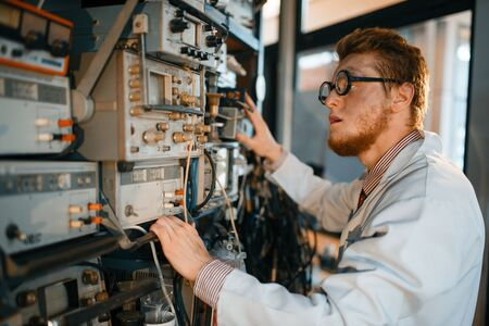 Scientist adjusts electrical device in laboratory