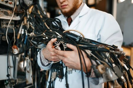 Engineer holds bunch of wires in laboratory