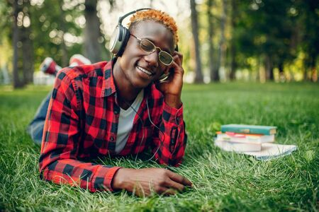 Black student in headphones resting on the grass