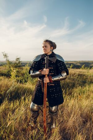 Female medieval knight poses in armor