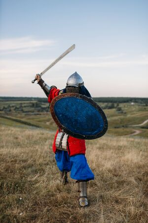 Medieval knight with sword poses in armor, fighter Stock Photo