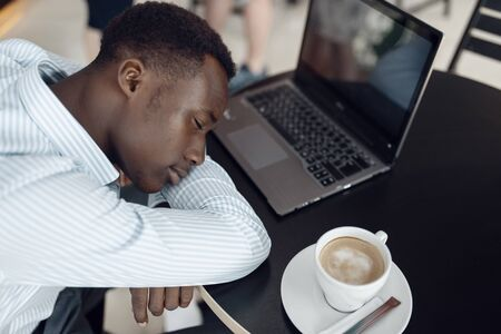 Businessman with laptop sleeping in office cafe
