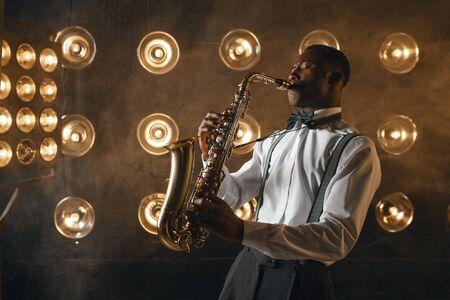 Un artiste de jazz noir joue du saxophone sur scène avec des projecteurs. Jazzman noir se produisant sur scène Banque d'images