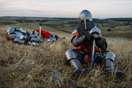 Medieval knight in armor sitting on the ground Banco de Imagens