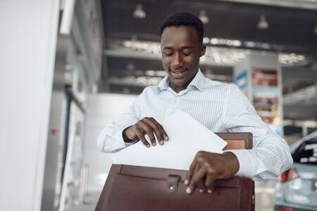 Negro businessman holds briefcase in car showroom Reklamní fotografie