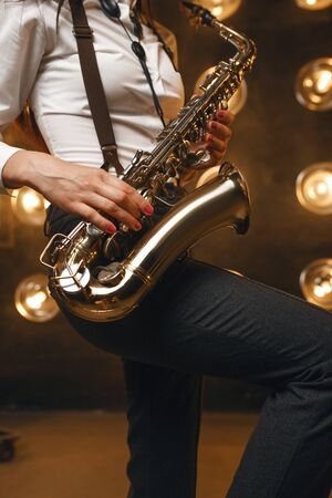 Female saxophonist plays the saxophone on stage