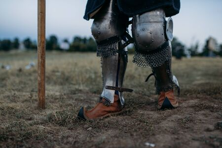 Medieval knight legs in metal armor, back view