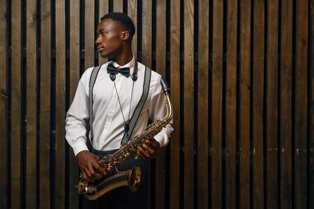 Jazz performer with saxophone, wooden background