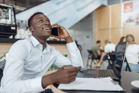 Ebony businessman talking by phone in office cafe
