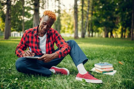 Black student writing in notebook on the grass Reklamní fotografie