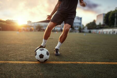 Male football player hits the ball on the field. Footballer on outdoor stadium, workout before competition, soccer training 免版税图像