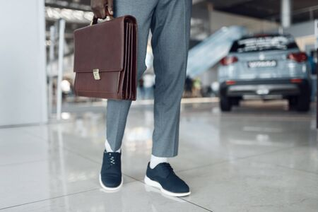 Businessman holds briefcase in car showroom