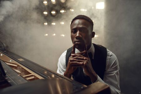 Ebony grand piano musician poses on the stage
