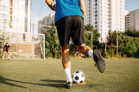 Male soccer player hits the ball on the field. Footballer on outdoor stadium, workout before game, football training Stok Fotoğraf - 132034819