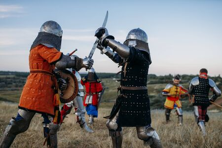 Medieval knights in armour and helmets fight with swords. Armored ancient warriors posing in the meadow
