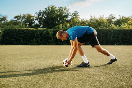 Male soccer player prepares to hits the ball on the field. Footballer on outdoor stadium, workout before game, football training