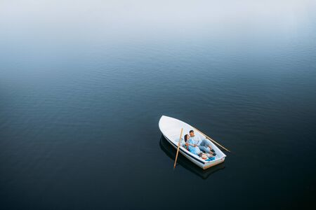 Love couple lying in a boat on lake, top view Reklamní fotografie