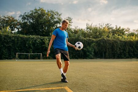 Male soccer player stuffs the ball with his foot Banco de Imagens - 132031426