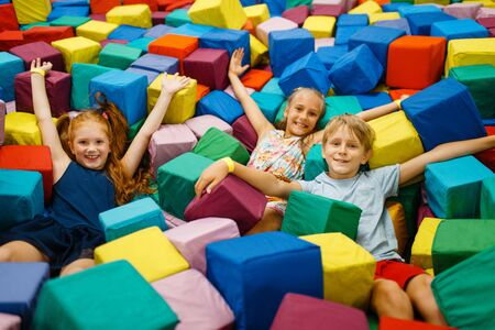 Happy children lying in soft cubes, playroom Stock Photo - 132114865