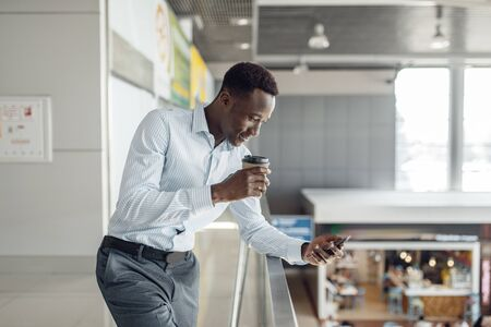 Black businessman with cup of coffee, food-court