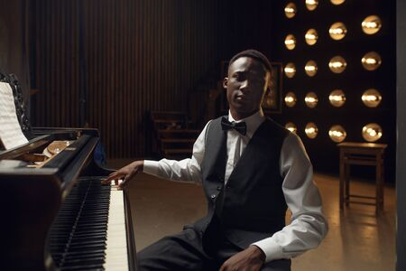 Ebony grand piano player on the stage