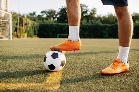 Male soccer player legs with ball standing on line on the field. Footballer on outdoor stadium, workout before football match Banco de Imagens - 132032715