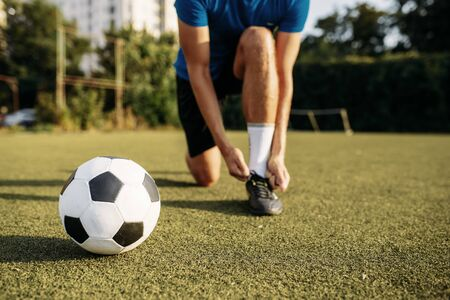 Male soccer player ties his shoelaces on boots, top view. Footballer on outdoor stadium, workout before game, football training Banco de Imagens - 132033251