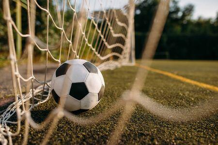 Soccer ball in the gate net, nobody. Football on outdoor stadium, sport game or goal concept Banco de Imagens - 132032793