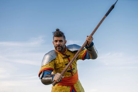 Old medieval knight in armor holds axe Stock Photo