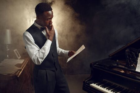 Black pianist with music notebook on the scene