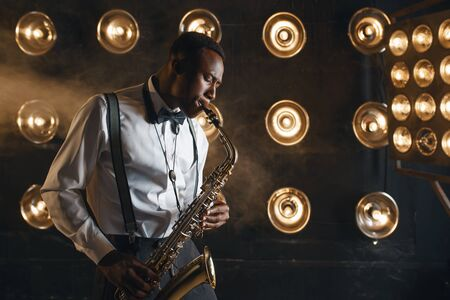Male jazzman plays the saxophone on stage