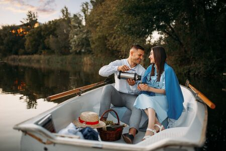 Love couple with thermos in a boat on quiet lake
