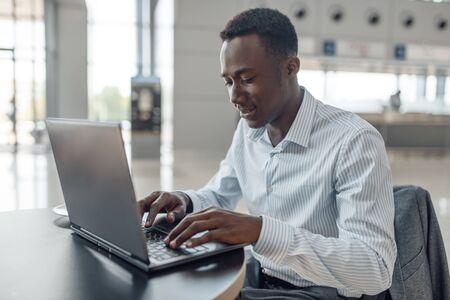 Businessman working on laptop in car showroom