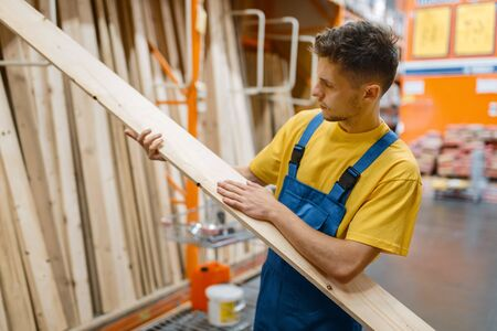 Constructor choosing wooden boards, hardware store